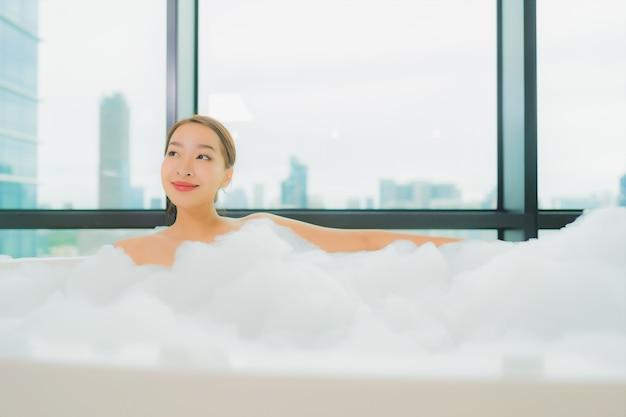 肖像画の美しい若いアジア女性はバスルームのインテリアでバスタブで笑顔レジャーをリラックスします。