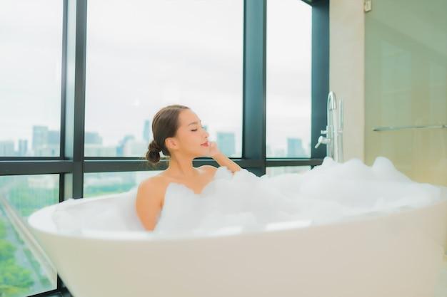 Женщина портрета красивая молодая азиатская ослабляет отдых улыбки в ванне в интерьере ванной комнаты