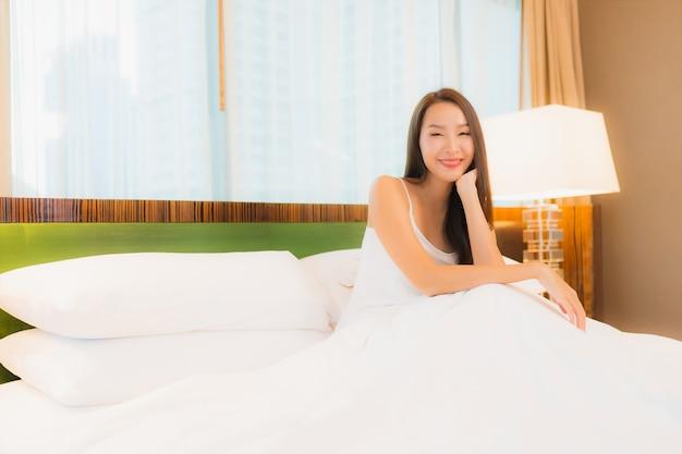 肖像画の美しい若いアジア女性は寝室のインテリアでベッドの上の笑顔をリラックスします。