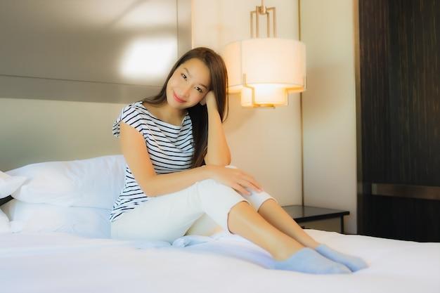 세로 아름 다운 젊은 아시아 여자 침실 인테리어에 침대에 미소를 긴장