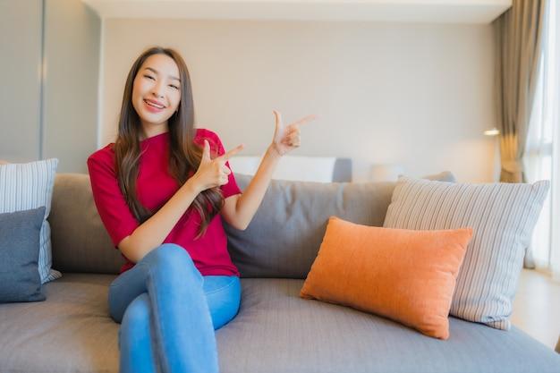 肖像画の美しい若いアジア女性はリビングエリアのソファーで笑顔をリラックスします。
