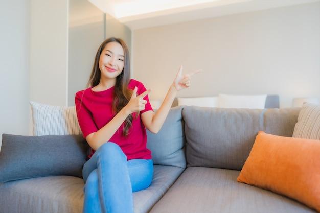 Женщина портрета красивая молодая азиатская ослабляет улыбку на софе в жилой зоне