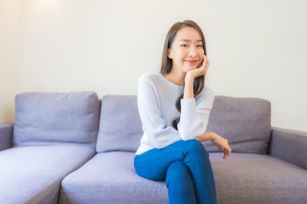 초상화 아름다운 젊은 아시아 여성은 거실에 있는 소파에서 미소를 지으며 휴식을 취합니다.