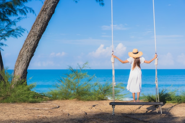 Женщина портрета красивая молодая азиатская ослабляет улыбку на качании вокруг океана моря пляжа для перемещения природы в каникулах