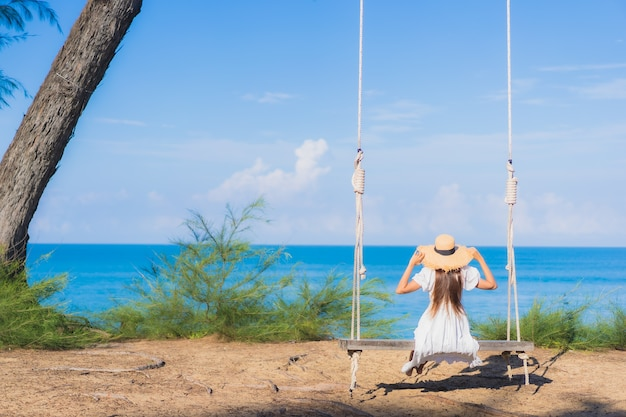 肖像画美しい若いアジアの女性は休暇中の自然旅行のためにビーチの海の海の周りのスイングで笑顔をリラックス