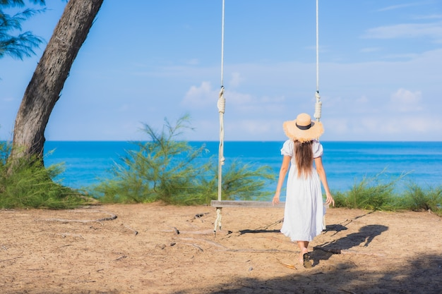 초상화 아름 다운 젊은 아시아 여자 휴가 자연 여행을위한 해변 바다 바다 주위 스윙에 미소를 휴식