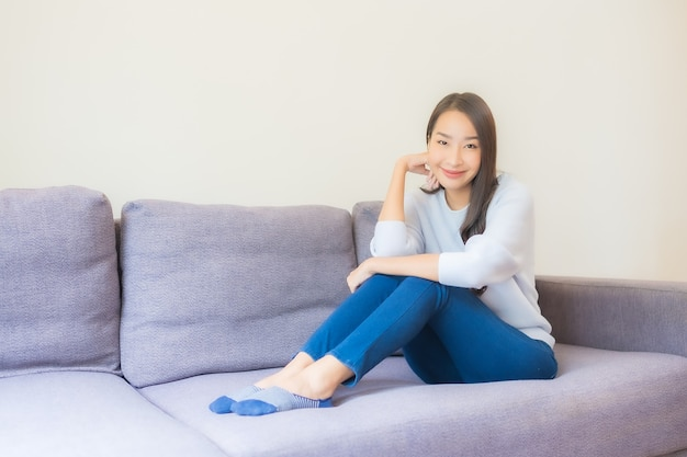 Portrait beautiful young asian woman relax smile on sofa in living room