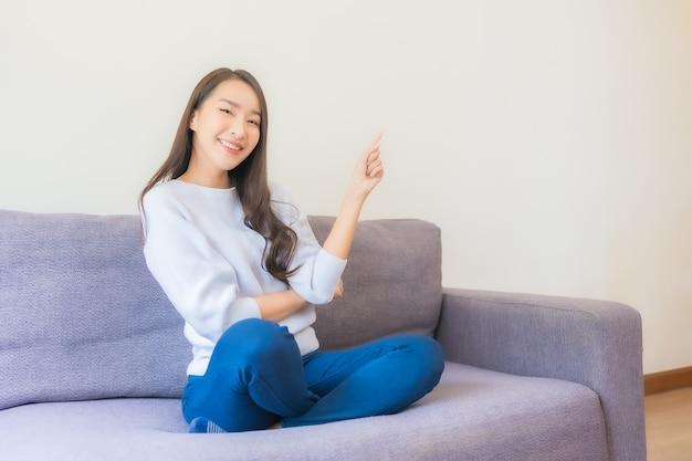 La bella giovane donna asiatica del ritratto si rilassa il sorriso sul sofà in soggiorno