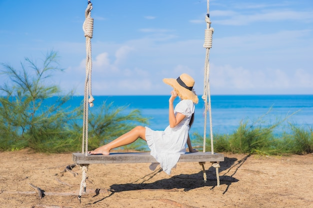 Portrait beautiful young asian woman relax smile on swing around beach sea ocean for nature travel in vacation