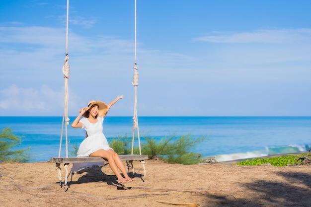 La bella giovane donna asiatica del ritratto si rilassa il sorriso sull'oscillazione intorno all'oceano del mare della spiaggia per il viaggio della natura in vacanza