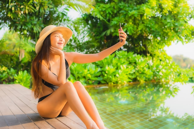 Portrait beautiful young asian woman relax in swimming pool at hotel resort for leisure vacation