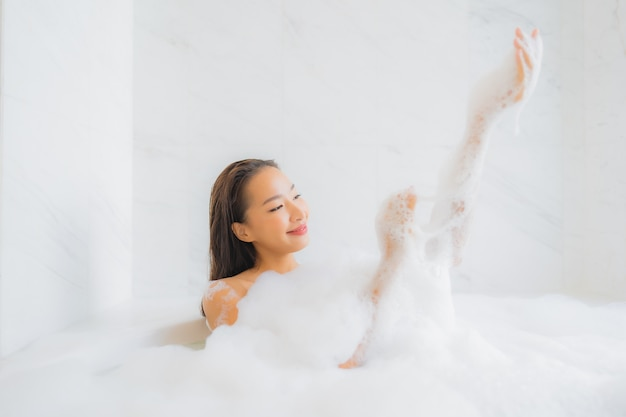 Portrait of beautiful young asian woman relaxes in bathtub