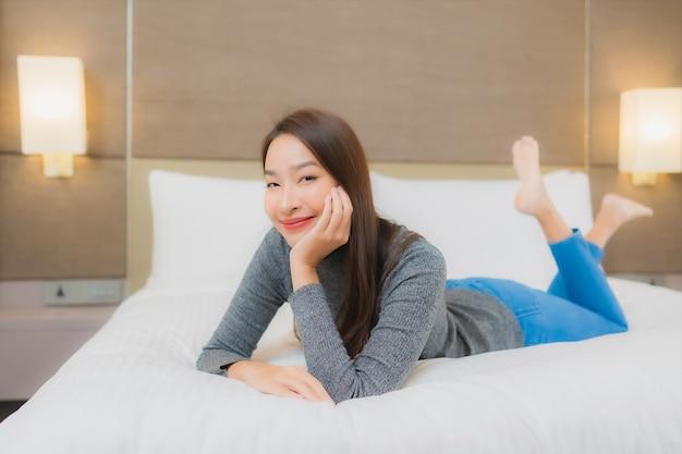 Ritratto di bella giovane donna asiatica si rilassa sul letto in camera da letto