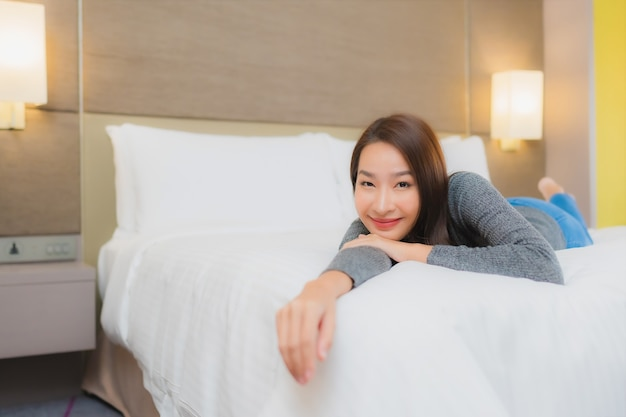 Portrait of beautiful young asian woman relaxes on bed in bedroom