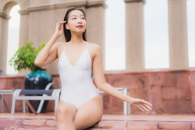 Portrait of beautiful young asian woman relaxes in the pool