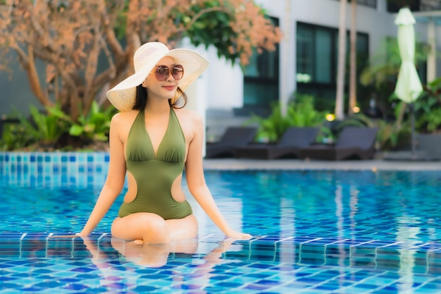 Portrait of beautiful young asian woman relaxes in swimming pool in hotel resort