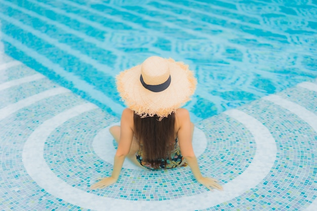 Portrait of beautiful young asian woman relaxes on the swimming pool in hotel resort