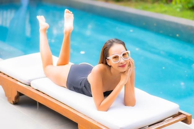Il ritratto di bella giovane donna asiatica si rilassa nella piscina
