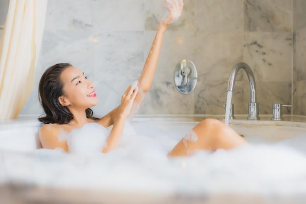 肖像画の美しい若いアジア女性はお風呂に入るリラックスします
