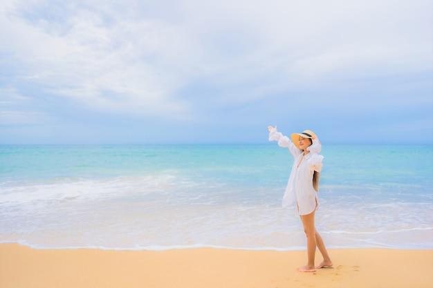 Ritratto di bella giovane donna asiatica che si rilassa intorno all'oceano del mare della spiaggia nella vacanza di viaggio