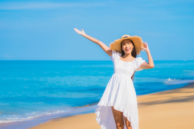 Portrait of beautiful young asian woman relaxing around beach with white clouds on blue sky in travel vacation