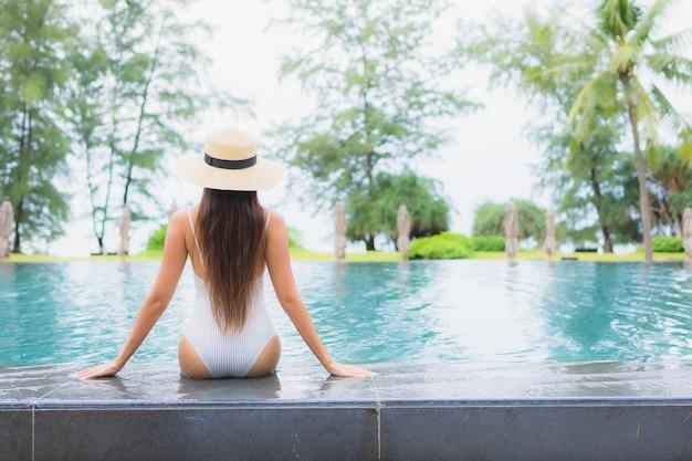 Ritratto di bella giovane donna asiatica che si rilassa intorno alla piscina all'aperto nella località di soggiorno dell'hotel quasi mare