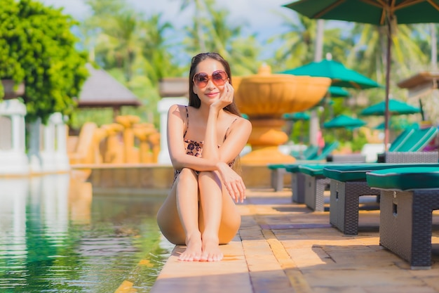 Portrait of beautiful young asian woman relaxing around outdoor swimming pool in hotel resort