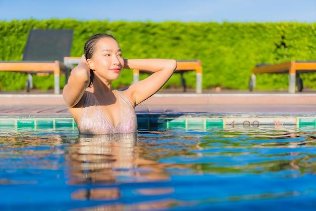 Ritratto di bella giovane donna asiatica che si rilassa intorno alla piscina all'aperto nella località di soggiorno dell'hotel