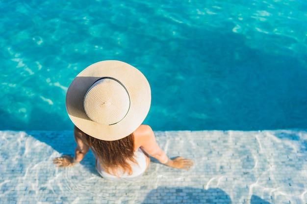 Женщина портрета красивая молодая азиатская ослабляя вокруг открытого бассейна с видом на город