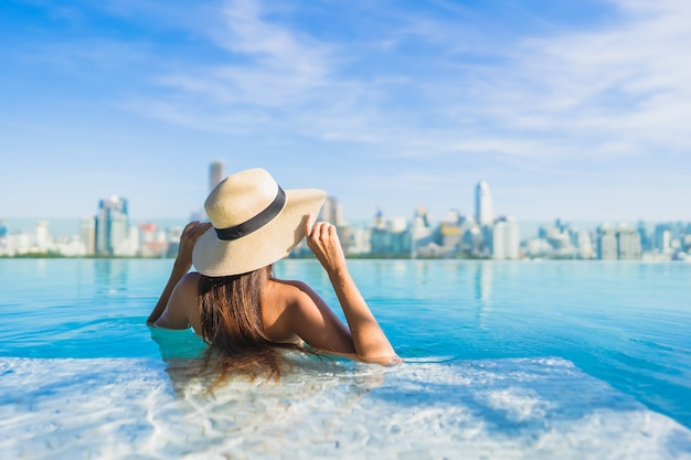 Portrait beautiful young asian woman relaxing around outdoor swimming pool with city view