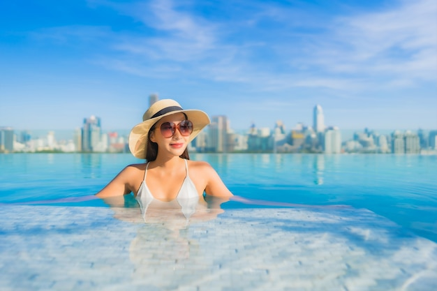 街の景色を望む屋外スイミングプールの周りでリラックスして美しい若いアジアの女性