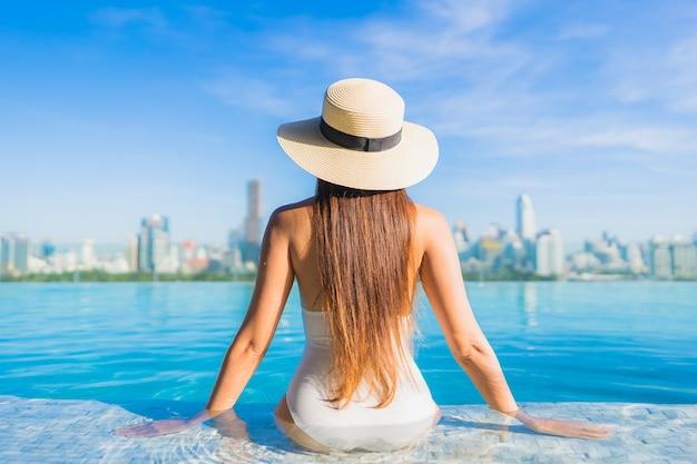 도시 전망과 야외 수영장 주변에서 편안한 초상화 아름 다운 젊은 아시아 여자