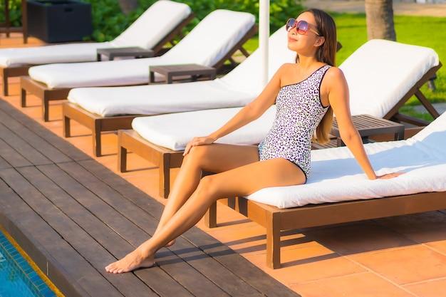 휴가에 리조트 호텔의 수영장 주변에서 휴식을 취하는 아름다운 젊은 아시아 여성 초상화
