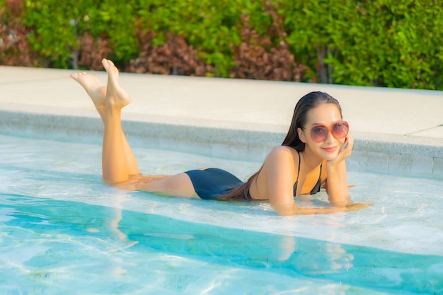 Portrait beautiful young asian woman relaxing around swimming pool in resort hotel on vacation