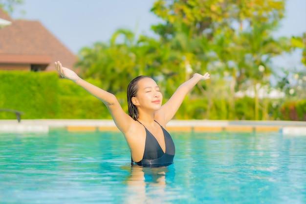 Ritratto bella giovane donna asiatica che si rilassa intorno alla piscina in hotel resort in vacanza