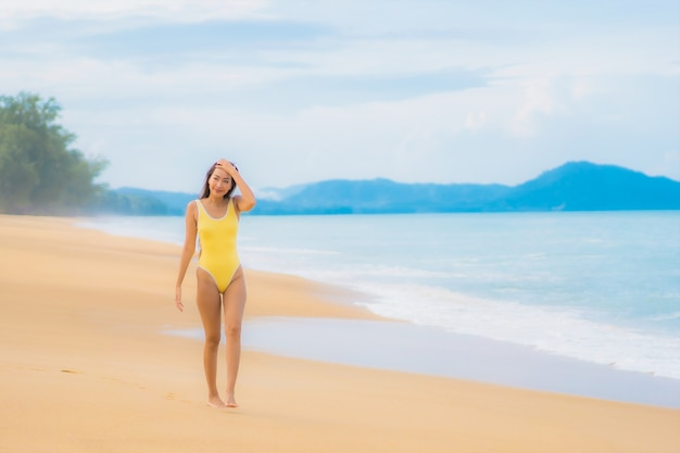 Portrait of beautiful young asian woman relaxing in the beach in travel vacation