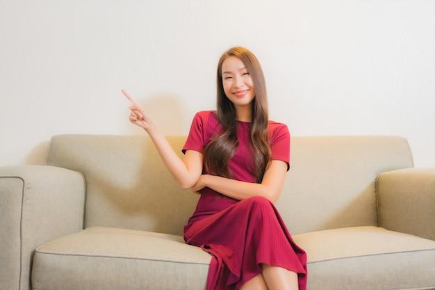 リビングルームのインテリアのソファでリラックスして美しい若いアジアの女性