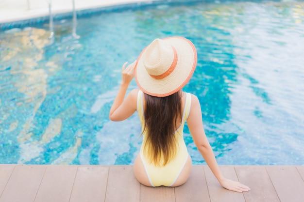 休暇旅行のプールで屋外でリラックスして美しい若いアジア人女性
