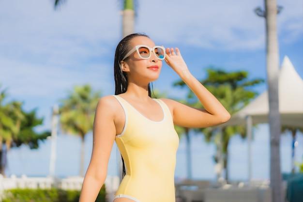 Bella giovane donna asiatica del ritratto che si rilassa all'aperto nella piscina in viaggio di festa