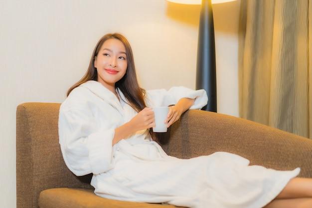 Bella giovane donna asiatica del ritratto che si rilassa sul sofà nell'interno del salone