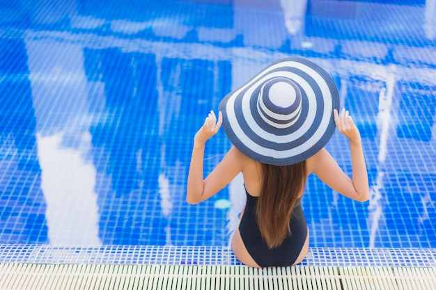 Portrait of beautiful young asian woman relaxinging around outdoor swimming pool in hotel resort