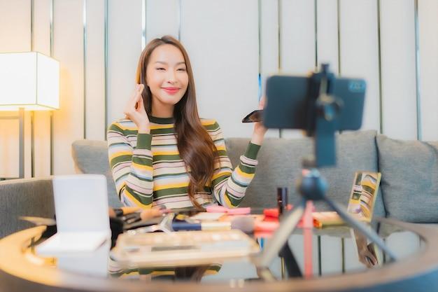 Ritratto di bella giovane donna asiatica recensioni e utilizza cosmetici sul divano