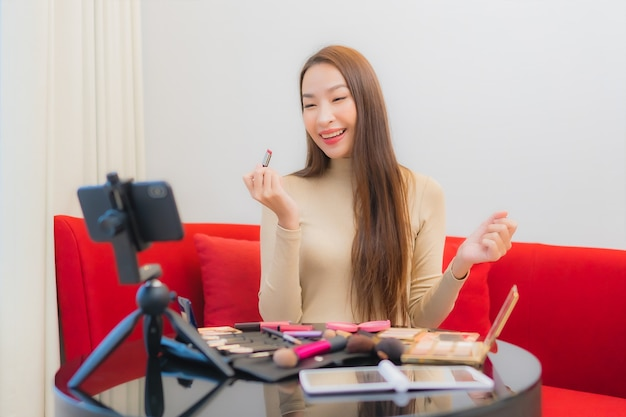 Portrait of beautiful young asian woman reviews and uses cosmetics on sofa
