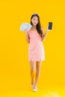 肖像画の美しい若いアジアの女性はモバイルスマートフォンでたくさんの現金とお金を表示します。
