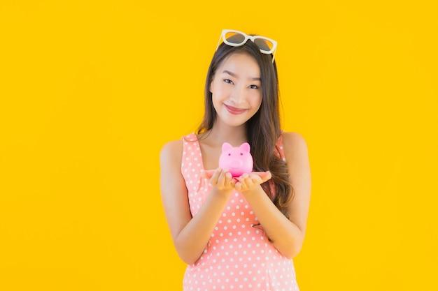 초상화 아름 다운 젊은 아시아 여자 돼지 저금통으로 현금 또는 돈을 많이 보여