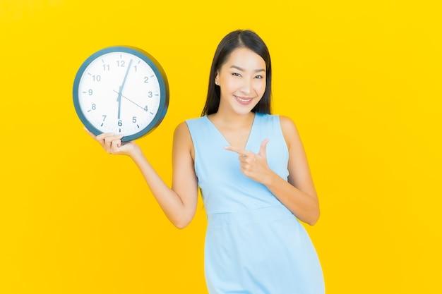 노란색 벽에 세로 아름 다운 젊은 아시아 여자 쇼 알람 또는 시계