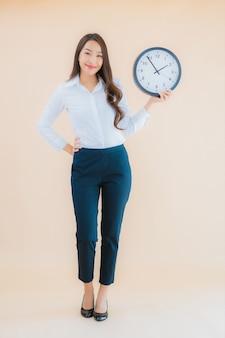 Будильник или часы выставки женщины портрета красивые молодые азиатские
