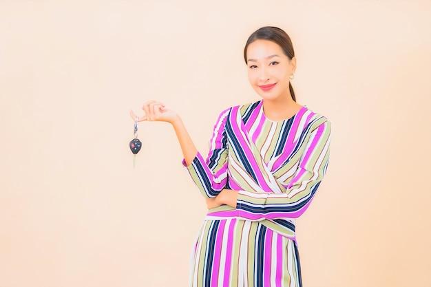 Bella giovane donna asiatica del ritratto mostra la chiave dell'auto sul colore