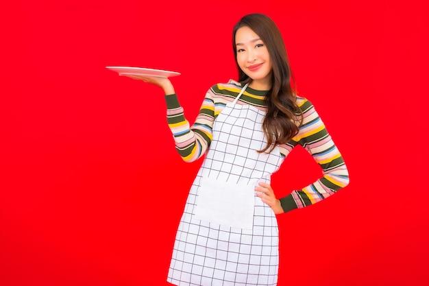 Блюдо выставки красивой молодой азиатской женщины портрета пустое на красной стене
