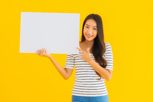 肖像画の美しい若いアジア女性は空の白い看板サインを表示します。